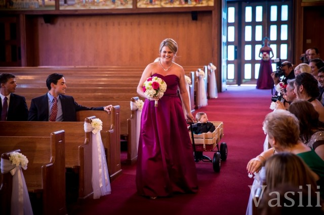 image of bridesmaid walking down isle pulling a wagon with a baby